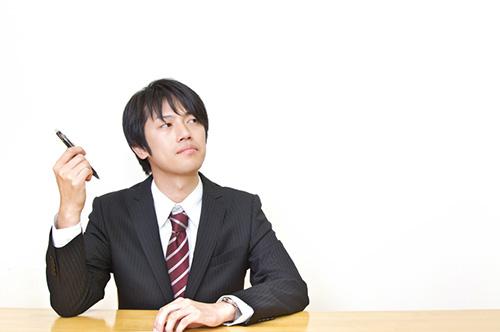 ペンを持ち考えるスーツ姿の男性 Tsuyoshi.