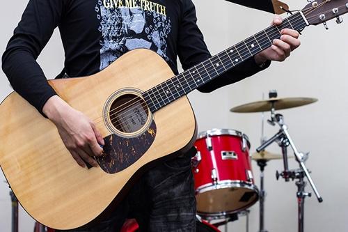 アコースティックギターを持つバンドマン