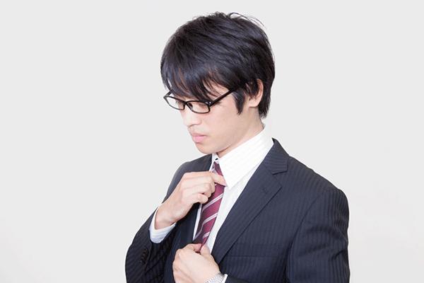 ネクタイを直す眼鏡をかけたサラリーマン