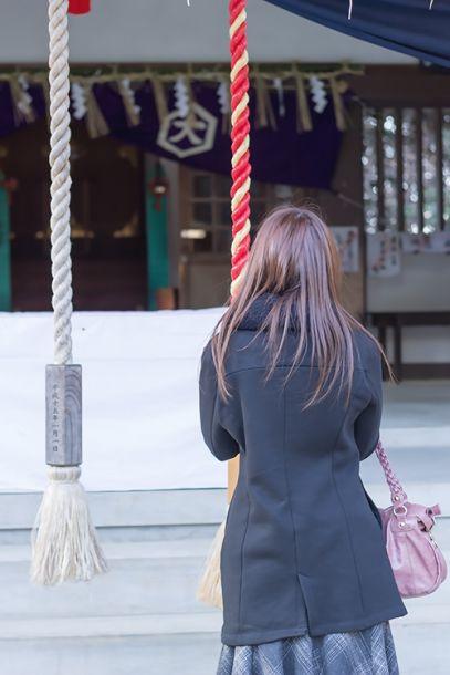 神社で参拝する女性