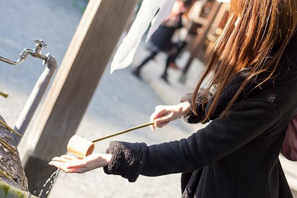 神社で手水をする女性