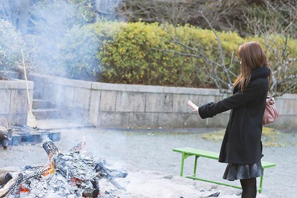 焚火で温まる女性